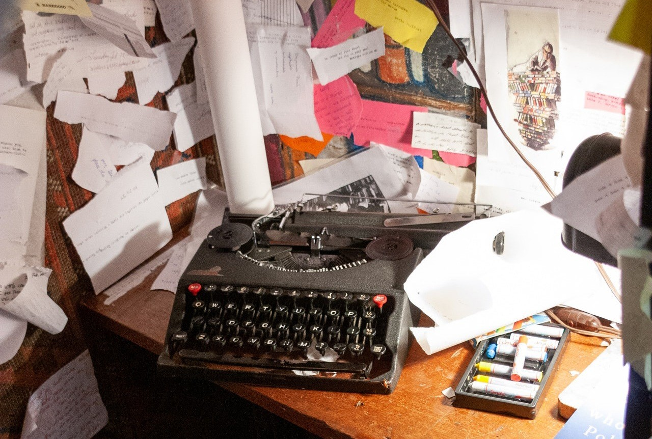 A typewriter on a messy desk surrounded by a corkboard with lots of notes on it.