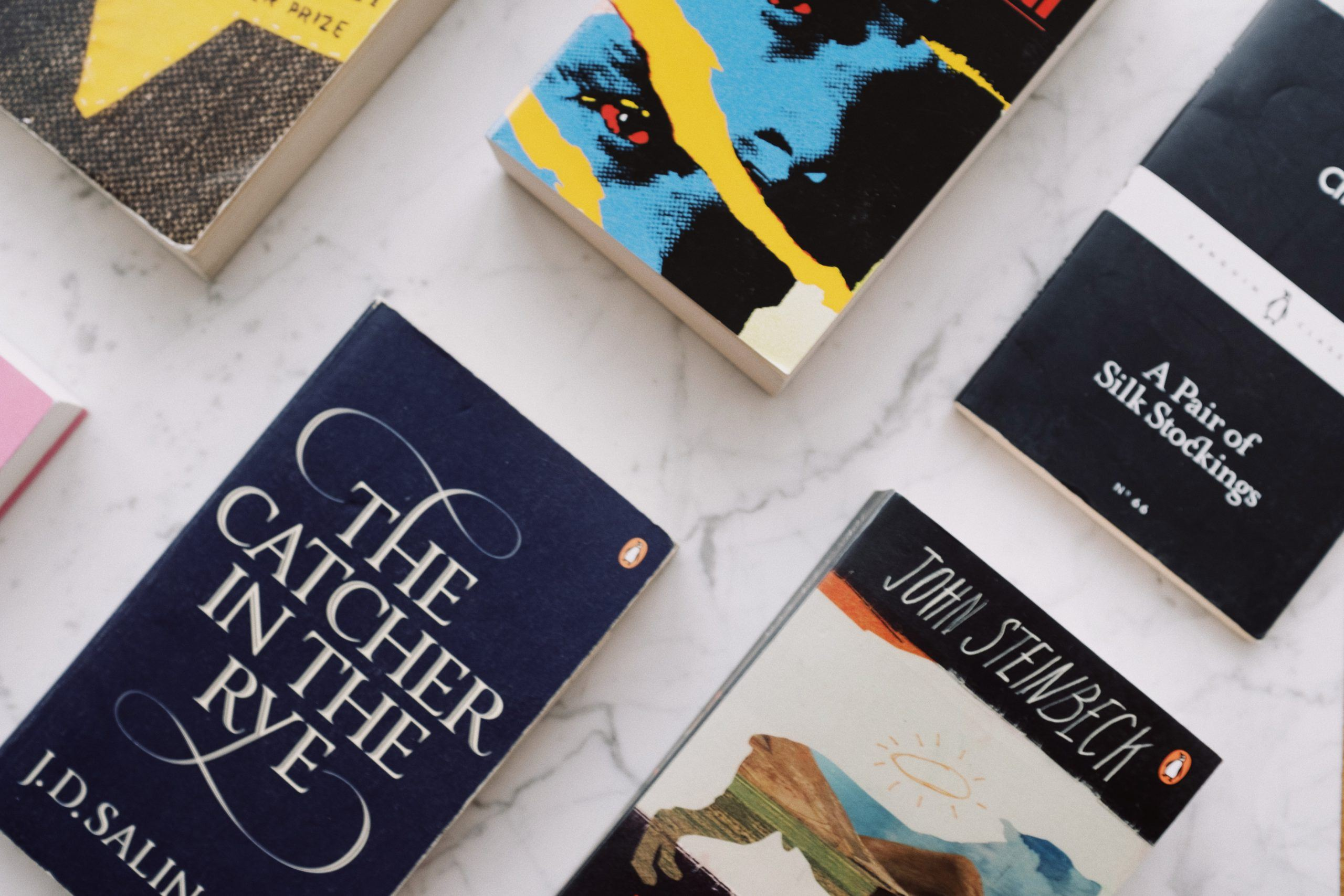Books laid out in a grid, including The Catcher in the Rye and A Pair of Silk Stockings.